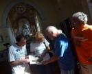 Tre volontari ci mostrano la foto del Polittico